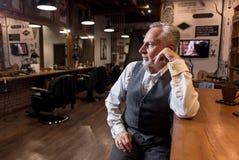 Starszy biznesmena obsiadanie przy baru kontuarem i patrzeć na boku Zdjęcie Stock