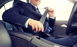 Starszy biznesmena uczepienia samochodu pas bezpiecze?stwa obrazy stock