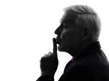 Starszy biznesowego mężczyzna palec na wargi sylwetce fotografia stock