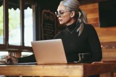 Starszy bizneswoman pracuje przy sklep z kawą zdjęcie royalty free