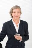 Starszy bizneswomanu uśmiechu chwyta telefon komórkowy Zdjęcia Royalty Free