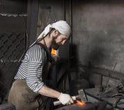 Starszy blacksmith skucie stopiony metal na kowadle w kowalu obraz royalty free
