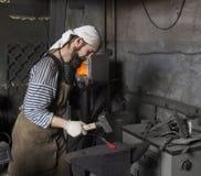 Starszy blacksmith skucie stopiony metal na kowadle w kowalu fotografia royalty free