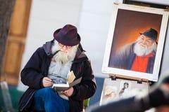 Starszy brodaty artysta pracuje przy sławnym miejscem Du Tertre w Montmartre fotografia stock