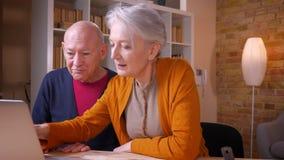 Starszy caucasian koledzy pracuje wpólnie na laptopie w biurze zbiory