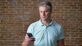 Starszy caucasian mężczyzna skupia się na pisać na maszynie w telefonie komórkowym spokojnie i pozycji w czerwony pracowniany sam