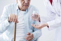 Starszy chory mężczyzna i pielęgniarka daje medycynie zdjęcia royalty free