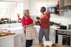Starszy czarny pary otwarcia szampan i śmiać się wpólnie w kuchni podczas gdy przygotowywający gościa restauracji na święto bożęg fotografia royalty free