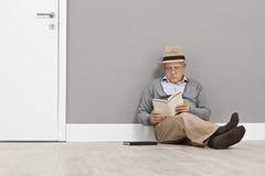 Starszy czytanie książka sadzająca na podłoga Zdjęcie Stock