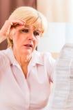 Starszy czytanie z presbyopia pakunku wszywką Fotografia Royalty Free