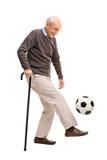 Starszy dżentelmen żongluje futbol Fotografia Stock