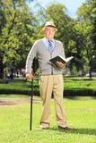 Starszy dżentelmen czyta książkę i patrzeje kamerę w parku Obrazy Royalty Free