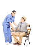 Starszy dżentelmen sadzający na ławce opowiada męska pielęgniarka Fotografia Stock