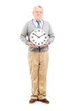 Starszy dżentelmen trzyma dużego ściennego zegar Obraz Royalty Free
