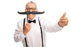 Starszy dżentelmen z dużym sfałszowanym wąsem up i kciukiem Fotografia Royalty Free