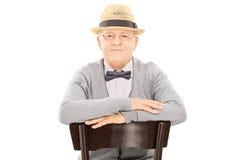 Starszy dżentelmen z kapeluszowym obsiadaniem na krześle Obraz Stock