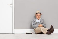 Starszy dżentelmenu dosypianie sadzający na podłoga Zdjęcia Stock