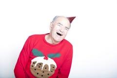 Starszy dorosły mężczyzna jest ubranym Bożenarodzeniową bluzę i czerwonego partyjnego kapelusz obraz stock