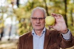 Starszy dorosły mienie zieleni jabłko Zdjęcia Royalty Free