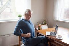 Starszy działanie na komputerze ma niskiego ból pleców obrazy royalty free