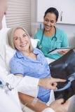 Starszy Żeński pacjent Z promieniowania rentgenowskiego, pielęgniarki i samiec lekarką, zdjęcia stock