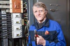 Starszy elektryk stoi blisko wysokiego woltażu panelu z cążkami w jego rękach obraz stock