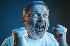 Starszy emocjonalny gniewny mężczyzna krzyczy na błękitnym pracownianym tle Fotografia Stock