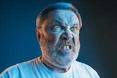Starszy emocjonalny gniewny mężczyzna krzyczy na błękitnym pracownianym tle Zdjęcie Stock