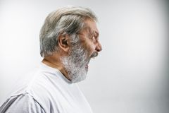 Starszy emocjonalny gniewny mężczyzna krzyczy na białym pracownianym tle Zdjęcie Stock