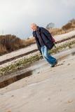Starszy energiczny mężczyzna bieg wzdłuż plaży obrazy stock