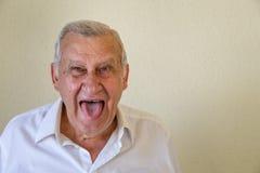 Starszy facet wtyka out jęzor Obraz Royalty Free