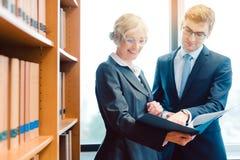 Starszy i młodzieżowy prawnik w firmie prawniczej dyskutuje strategię w skrzynce zdjęcie stock