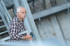 Starszy inżynier patrzeje w fabrykę od outside Zdjęcie Stock