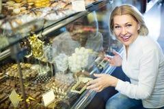 Starszy klient wybiera czekolady fotografia stock