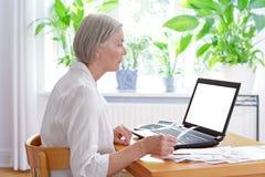 Starszy kobieta laptop wystawia rachunek kwity fotografia royalty free