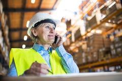 Starszy kobieta magazynu kierownik lub nadzorca z smartphone, robi rozmowie telefonicza Obrazy Stock