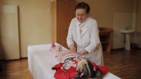 Starszy kobieta masażysta robi masażowi podbrzusze mała dziewczynka w szpitalu zbiory wideo
