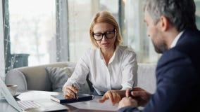 Starszy kobieta przedsiębiorca negocjuje kontrakt z partnerem biznesowym w kawiarni zdjęcie wideo