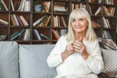 Starszy kobiety emerytura pojęcia obsiadanie pije herbacianych wspominki w domu Zdjęcia Royalty Free