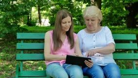 Starszy kobiety i młodej kobiety obsiadanie na ławce w parku, używać pastylka komputer Dorosły córki i matki używać zbiory