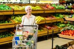 Starszy kobiety kładzenia banan w jej tramwaju fotografia stock