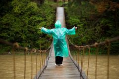 Starszy kobiety 60 lat Krzyżuje rzekę zależącym od mostem w lesie obrazy stock