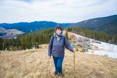 Starszy kobiety 60 lat wycieczkuje w górach z śnieżnym podziwia dolinnym widokiem zdjęcia stock
