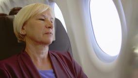 Starszy kobiety latanie w samolocie Męczący dżetowego opóźnienia żeńskim relaksującym pobliskim okno podczas turbulenci zbiory