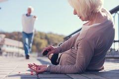 Starszy kobiety lying on the beach na dolewanie pigułkach i ziemi Obrazy Royalty Free