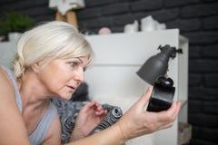 Starszy kobiety mienia budzik sprawdza out czas zdjęcia stock
