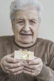 Starszy kobiety mienia prezent na ona ręki Zdjęcia Stock