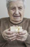 Starszy kobiety mienia prezent na ona ręki Zdjęcia Royalty Free