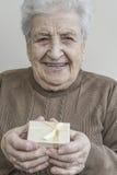 Starszy kobiety mienia prezent na ona ręki Zdjęcie Stock