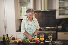 Starszy kobiety narządzania jedzenie cyfrową pastylką i wineglasses w kuchni Obrazy Stock